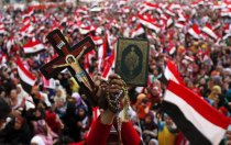 A demonstrator holds a cross and a Koran during a protest against ousted President Mursi at Tahrir Square in Cairo
